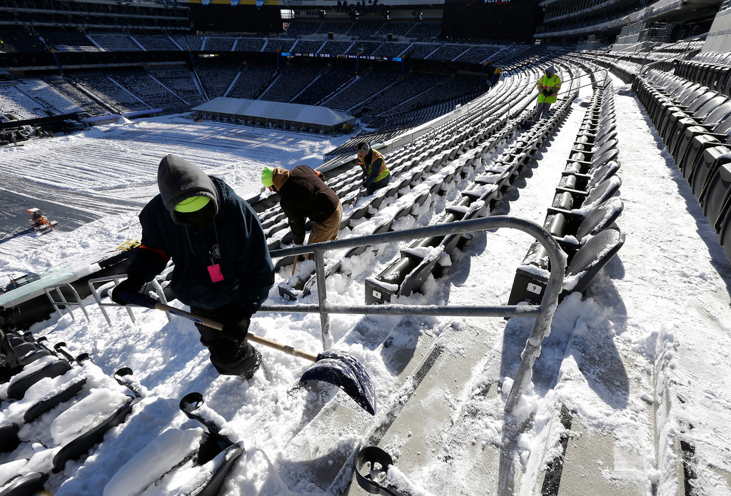 . Workers shovel snow off the seating area at MetLife Stadium as crews removed snow ahead of Super Bowl XLVIII following a snow storm, Wednesday, Jan. 22, 2014, in East Rutherford, N.J.  (AP Photo/Julio Cortez)