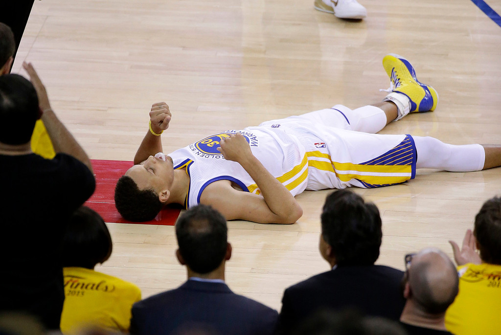 . Golden State Warriors guard Stephen Curry (30) lays on the floor during overtime of Game 1 of basketball\'s NBA Finals against the Cleveland Cavaliers in Oakland, Calif., Thursday, June 4, 2015. The Warriors won 108-100. (AP Photo/Eric Risberg)