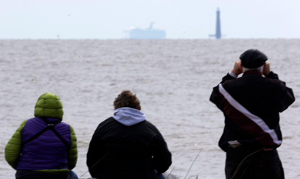 . Residents sit on the shore and watch as the cruise ship Carnival Triumph is visible near Dauphin Island, Ala., Thursday, Feb. 14, 2013. The ship with over 1,000 passengers aboard has been idled for nearly a week in the Gulf of Mexico following an engine room fire. (AP Photo/Dave Martin)