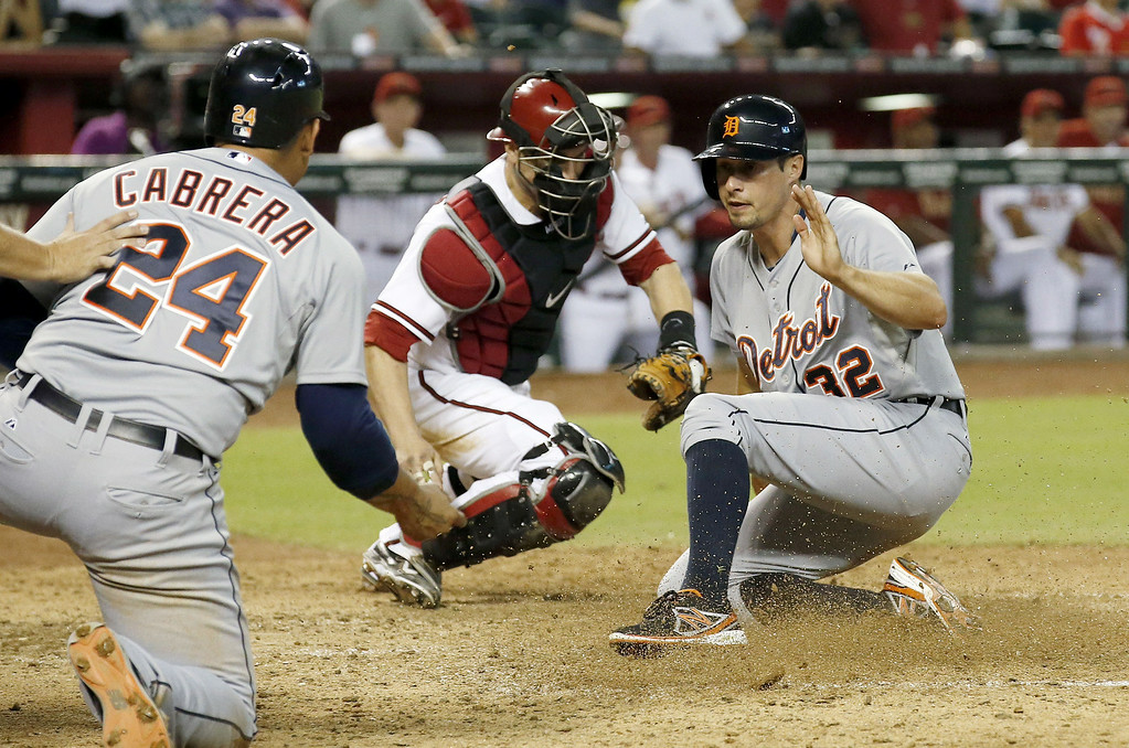 . Detroit Tigers\' Don Kelly (32) scores a run ahead of the tag by Arizona Diamondbacks\' Miguel Montero, middle, as Tigers\' Miguel Cabrera (24) looks on during the eighth inning of a baseball game on Tuesday, July 22, 2014, in Phoenix. (AP Photo)