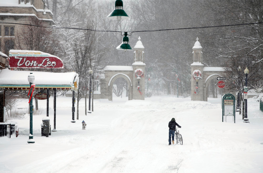 Description of . Heading toward Indiana University's Sample Gates, Yasukiko Aoliki  heads home after trekking downtown for a haircut only to find the business closed, Wednesday, Dec. 26, 2012 in Bloomington, Ind. (AP Photo/Bloomington Herald-Times, Jeremy Hogan)
