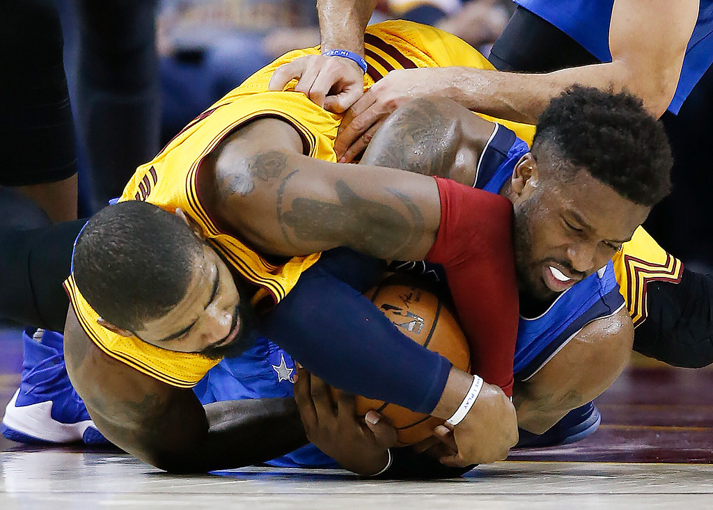. Cleveland Cavaliers\' Kyrie Irving, left, ties up Dallas Mavericks\' Wesley Matthews for a jump ball during the second half of an NBA basketball game Friday, Nov. 25, 2016, in Cleveland. The Cavaliers won 128-90. (AP Photo/Ron Schwane)