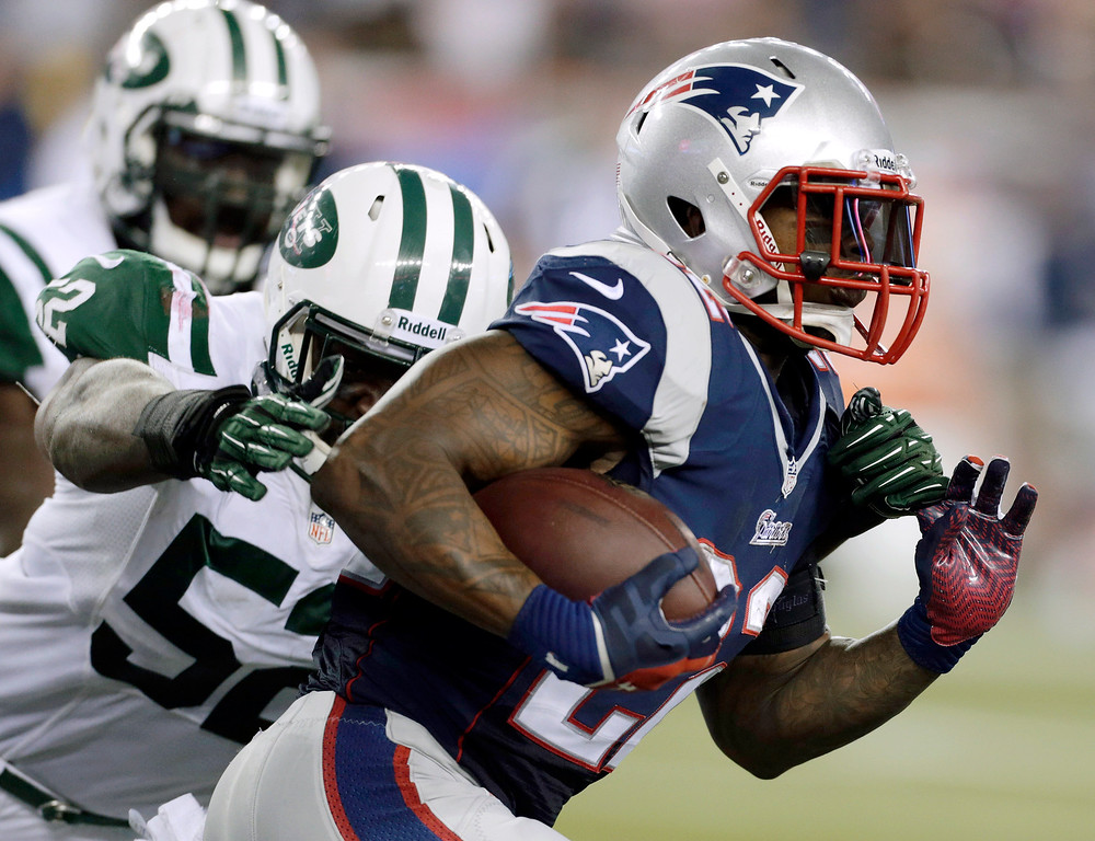 . New England Patriots running back Stevan Ridley (22) runs past New York Jets inside linebacker David Harris (52) during the first half of an NFL football game Thursday, Sept. 12, 2013, in Foxborough, Mass. (AP Photo/Charles Krupa)