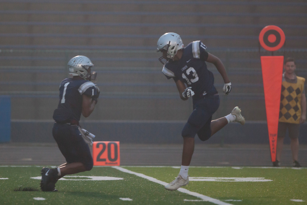 . Jen Forbus - The Morning Journal<br> Lorain\'s Tyshawn Lighty, left, intercepts a St. Joseph pass on Sept. 14.