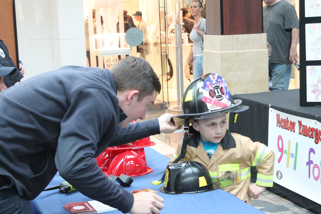 . Kristi Garabrandt � The News-Herald <br> Mentor Fire-medic Jesse Sopko helps helps Lincoln Clager,  4, Painesville,  try on a fire helmet  during the 36th Annual Heroes Day held at Great Lakes Mall, May 12, 2018.