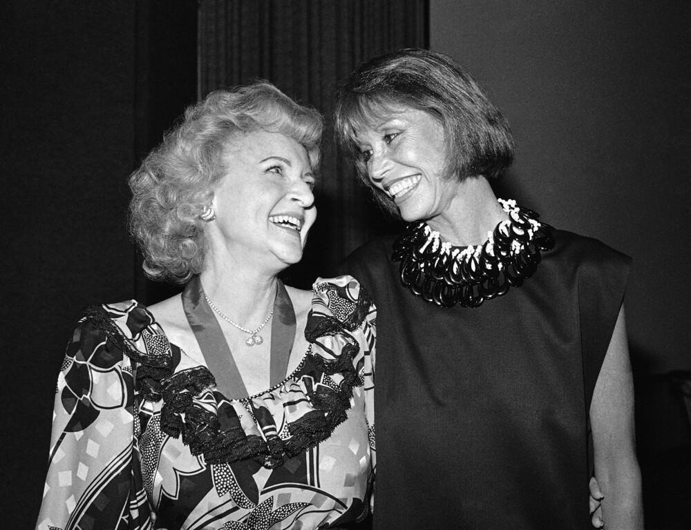 . Actresses Betty White Ludden, left, and Mary Tyler Moore, right, smile at each other in Los Angeles, Friday, June 22, 1985 during Annual Meeting of Morris Animal Foundation, at which Ludden announced her retirement as President of the animal health group, held at the Sheraton Universal Hotel in Los Angeles. (AP Photo/Nick Ut)