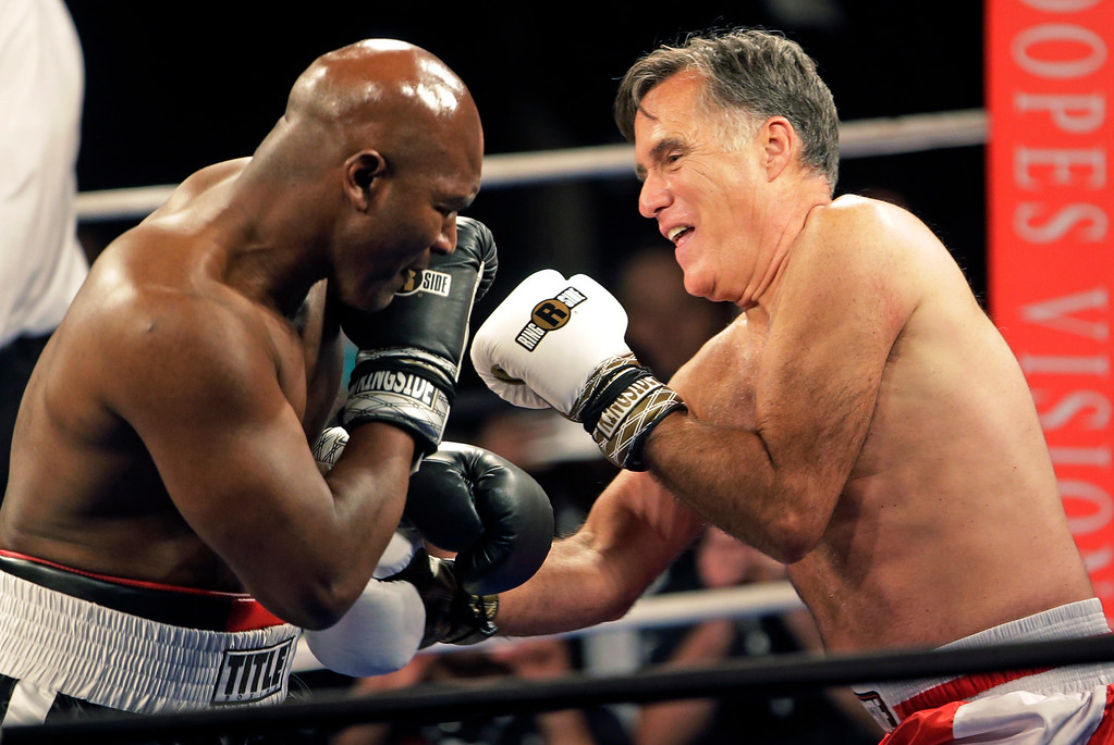 . Former Republican presidential candidate Mitt Romney, right, throws punches with five-time heavyweight boxing champion Evander Holyfield at a charity fight night event Friday, May 15, 2015, in Salt Lake City. The black-tie event will raise money for the Utah-based organization CharityVision, which helps doctors in developing countries perform surgeries to restore vision in people with curable blindness. (AP Photo/Rick Bowmer)