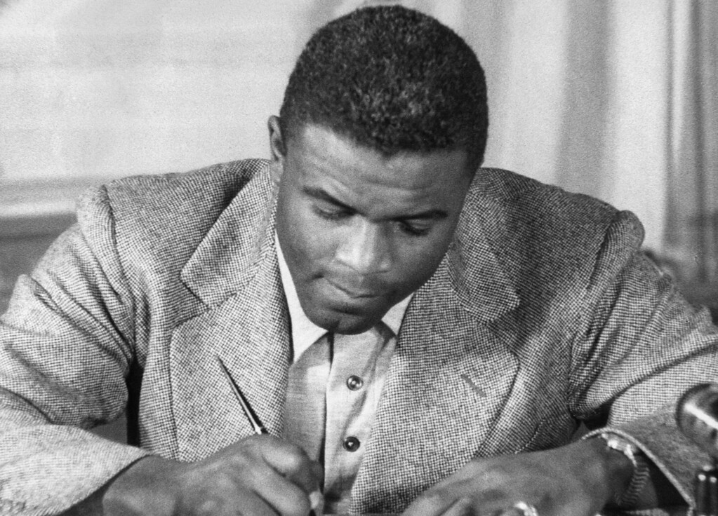 . Undated photo of US baseball star Jackie Robinson as he signs a then-record contract to play for the Brooklyn Dodgers. Robinson, who endured insults and death threats to integrate United States sports, was honored 15 April by the permanent retirement of his jersey number throughout Major League baseball. The contract, the highest salary in Dodger history up to then, was for US $35, 000 a year. (STR/AFP/Getty Images)