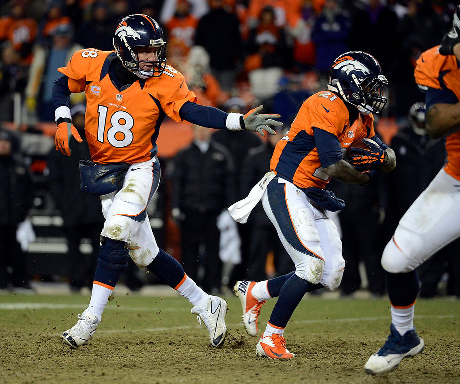 . Denver Broncos quarterback Peyton Manning (18) hands off to Denver Broncos running back Ronnie Hillman (21) during the second half.  The Denver Broncos vs Baltimore Ravens AFC Divisional playoff game at Sports Authority Field Saturday January 12, 2013. (Photo by Tim Rasmussen,/The Denver Post)