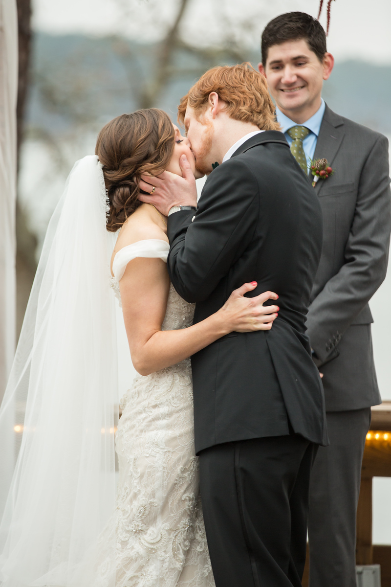 A bride and groom kissing at the end of their wedding ceremony