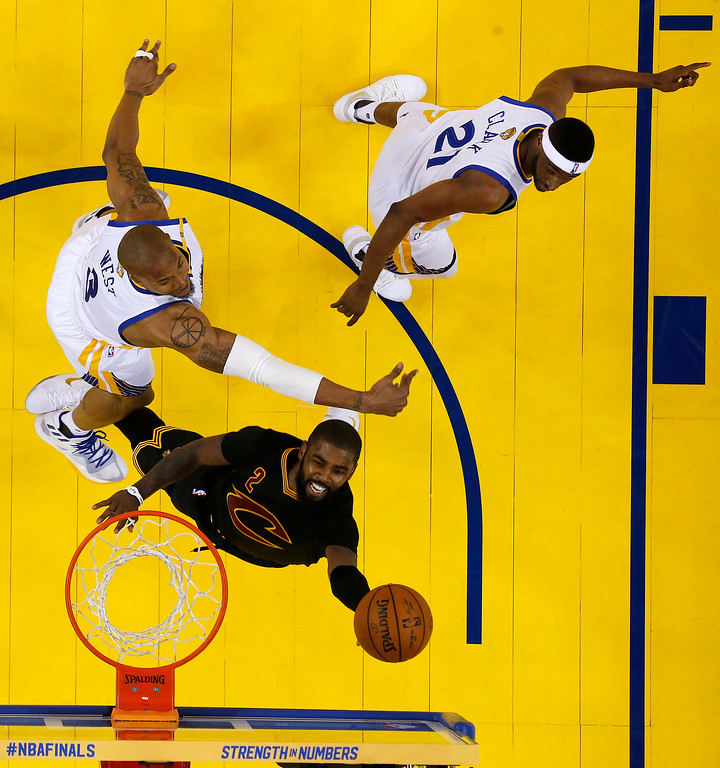 . Cleveland Cavaliers\' Kyrie Irving, bottom shoots past Golden State Warriors\' David West, left, and Ian Clark during the second half in Game 2 of basketball\'s NBA Finals Sunday, June 4, 2017, in Oakland, Calif. (AP Photo/Marcio Jose Sanchez, Pool)
