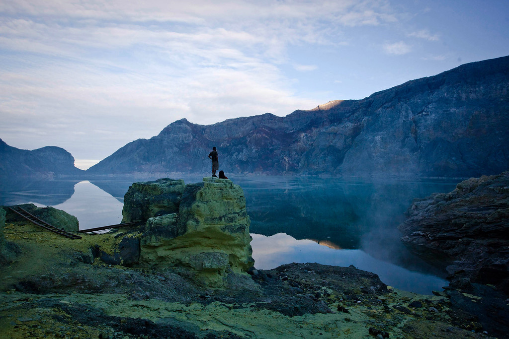 . A tourist stands on a rock watching the view of Ijen Crater during an annual offering ceremony on the Ijen volcano on December 17, 2013 in Yogyakarta, Indonesia.  (Photo by Ulet Ifansasti/Getty Images)
