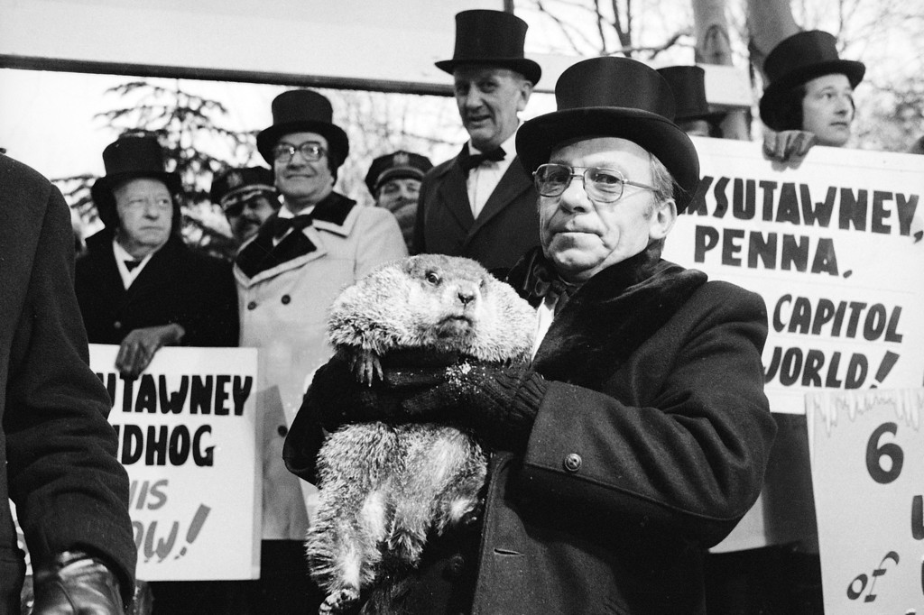 . Jim Means holds up a sleepy Punxsutawney Phil at daybreak, Feb. 2, 1980, in Punxsutawney, Penn., in front of a crowd of anxious people.  The groundhog saw his shadow and proclaimed six more weeks of winter.  Means cares for Phil throughout the year in the animal\'s home in the town library.  (AP Photo)
