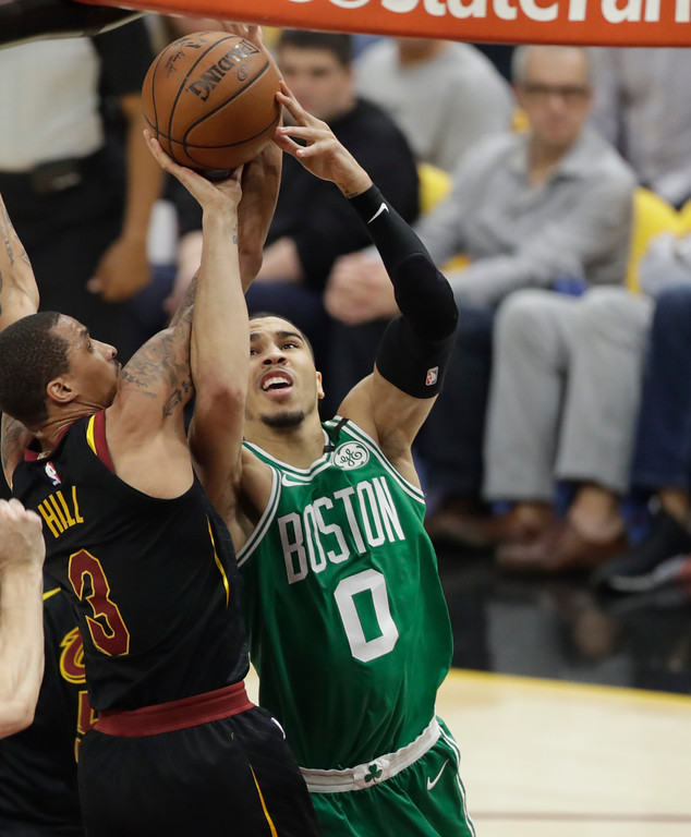 . Boston Celtics\' Jayson Tatum (0) drives to the basket as Cleveland Cavaliers\' George Hill (3) defends in the first half of Game 3 of the NBA basketball Eastern Conference finals, Saturday, May 19, 2018, in Cleveland. (AP Photo/Tony Dejak)