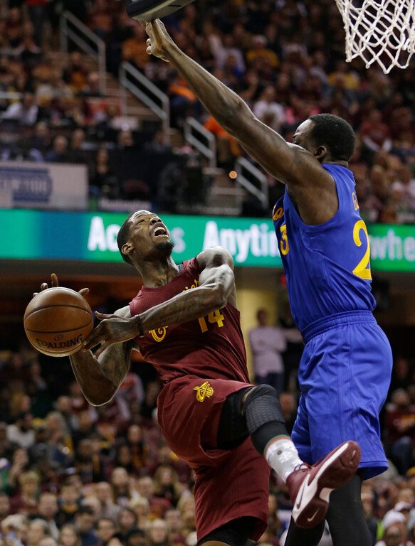 . Cleveland Cavaliers\' DeAndre Liggins (14) drives against Golden State Warriors\' Draymond Green (23) in the first half of an NBA basketball game, Sunday, Dec. 25, 2016, in Cleveland. (AP Photo/Tony Dejak)