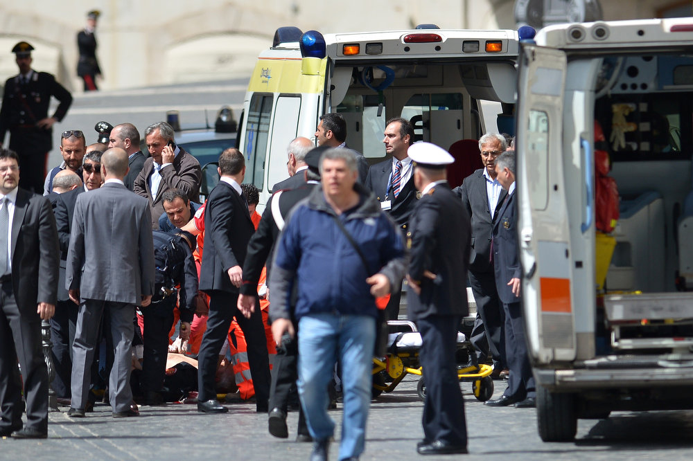 . A policeman receives assistance after being shot on April 28, 2013 in Rome, outside the palazzo Chigi, the Italian Prime minister offices, while the country\'s new ministers were being sworn in.   GABRIEL BOUYS/AFP/Getty Images