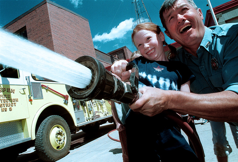 Aspen Elementary student Molly Rosenstein, 7, is helped by Jess Graber of the AVFD during a visit to the fire barn Tuesday morning May 7, 2002. The class of Jonathon DuPont experienced everything from sitting in the fire truck, the jaws of life adn sprying a fire hose. Paul Conrad photo.