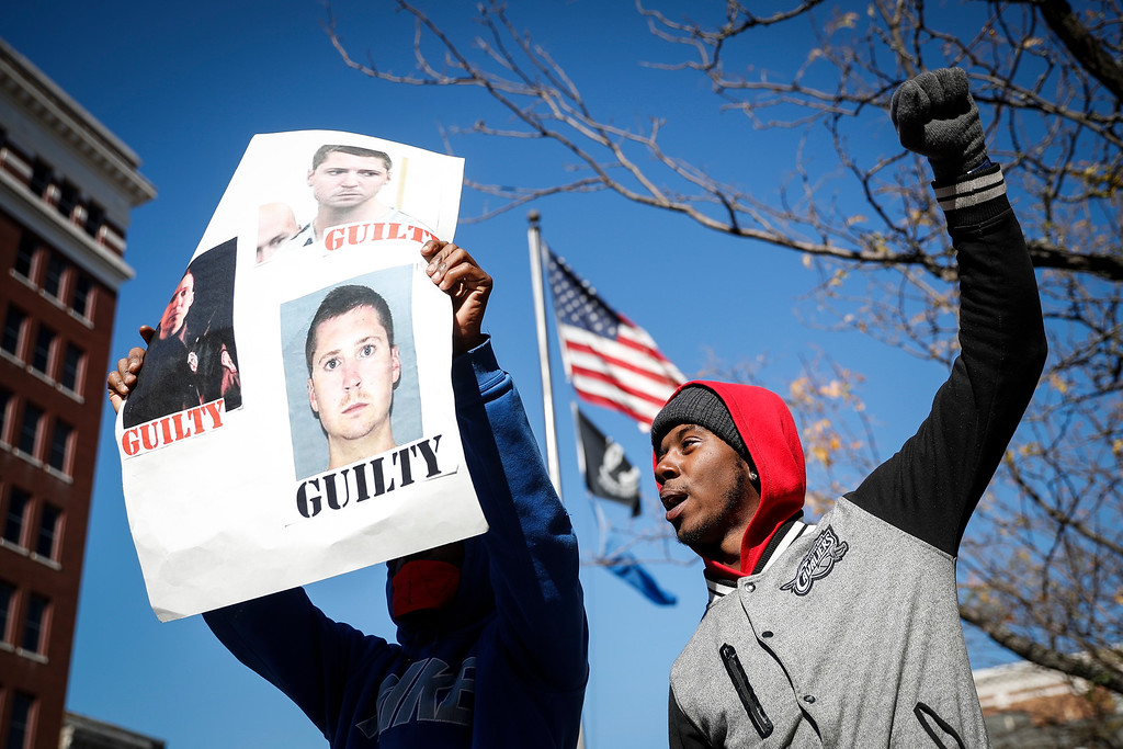 . Protestors chant outside the Hamilton County Courthouse after a mistrial is declared due to a hung jury in the murder trial against Ray Tensing, Saturday, Nov. 12, 2016, in Cincinnati. Tensing, a white former University of Cincinnati police officer, is charged with murder in the shooting of Sam DuBose, an unarmed black motorist, while on duty during a routine traffic stop on July 19, 2015. (AP Photo/John Minchillo)
