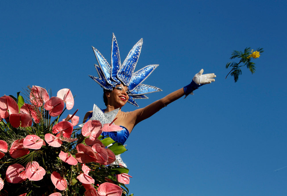 Description of . A woman dressed as a Liberty statue throws flowers during the Carnival parade in Nice February 16, 2013. The 129th Carnival of Nice runs from February 15 to March 6 and celebrates the
