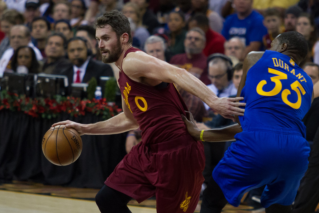 . The Cleveland Cavaliers\'  Kevin Love (0) drives past Kevin Durant (35) of the Golden State Warriors during an NBA game at the Quicken Loans Arena on Christmas day.  The Cavs defeated the Warriors 109-108.  Michael Johnson - The News Herald