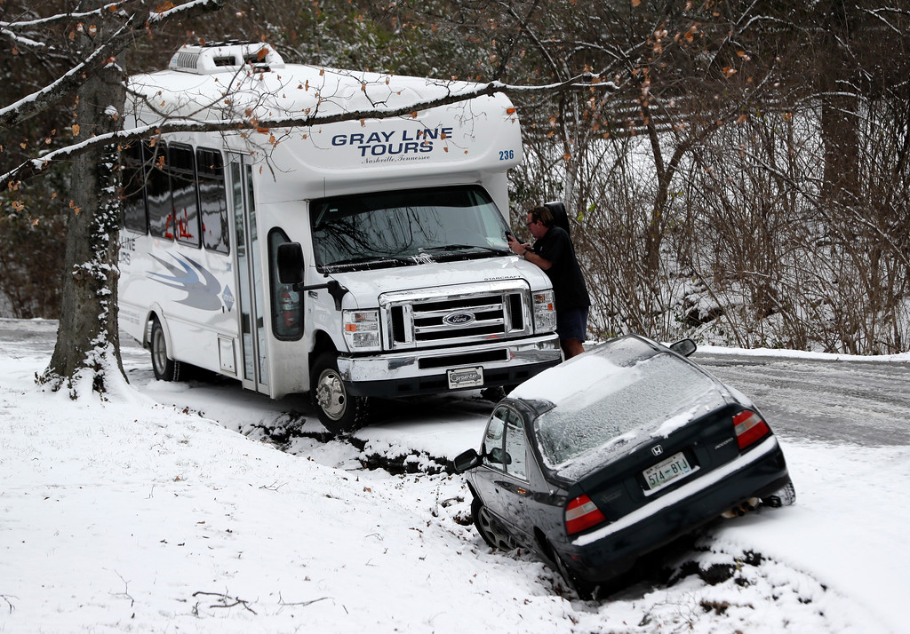 . A tour bus and a car sit in a ditch before being towed off a slick street Friday, Jan. 6, 2017, in Nashville, Tenn. Winter weather closed schools and made driving conditions hazardous in Nashville and other parts of the state. (AP Photo/Mark Humphrey)