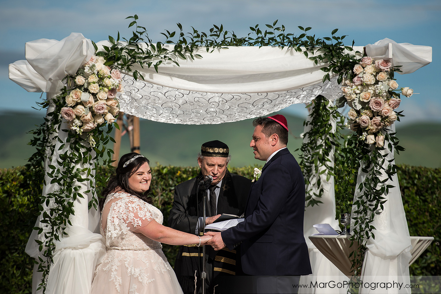 bride and groom holding hands during jewish wedding ceremony at Livermore Garre Vineyard and Winery