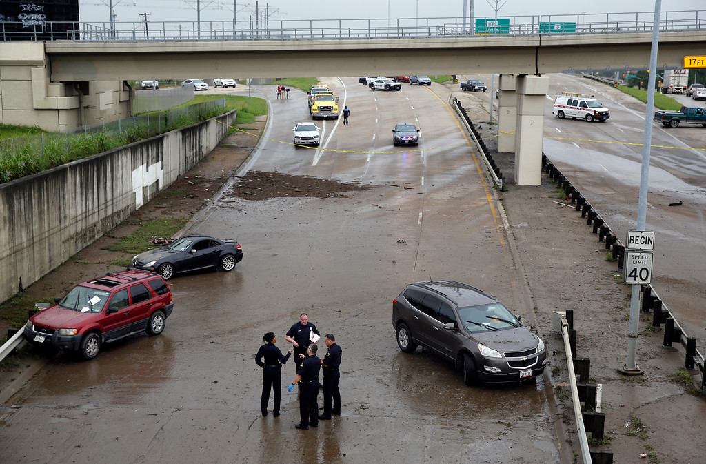 . Dallas police officers wait for a toll truck to take several vehicles from Northwest Highway close to Harry Hines Blvd. due to heavy rains on Friday, May 29, 2015 in Dallas. Floodwaters submerged highways and threatened homes Friday in Texas as another round of heavy rain added to the damage inflicted by storms. (David Woo/The Dallas Morning News via AP)