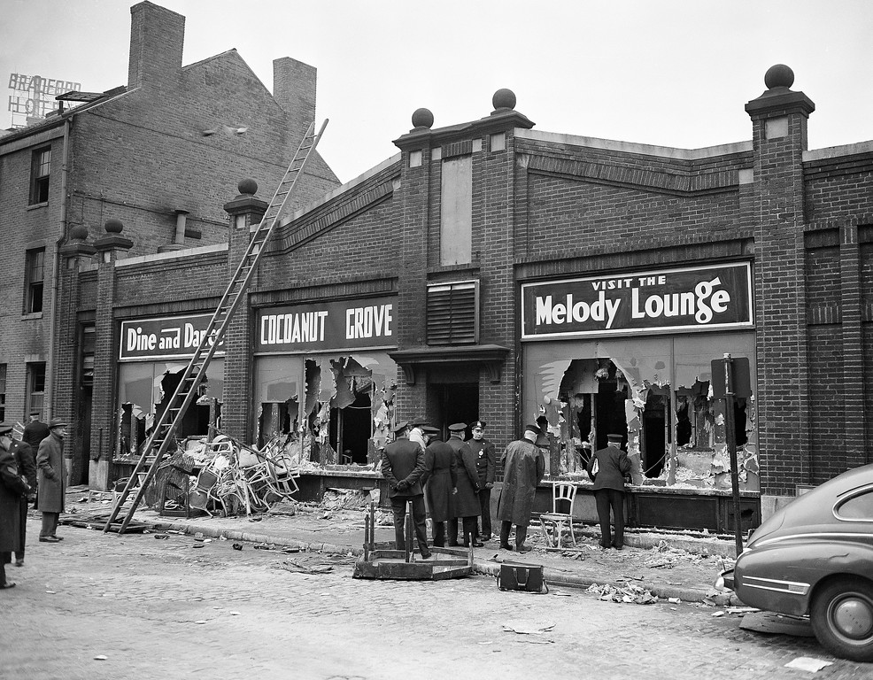 . Boston police and firemen watch rear entrance to the Melody Lounge section of the Cocoanut Grove Night Club, Nov. 29, 1942. Debris from broken chairs, table and personal effects of some guests of the club when the fire broke out last night litter sidewalk and gutter. Over 400 people perished.  (AP Photo)