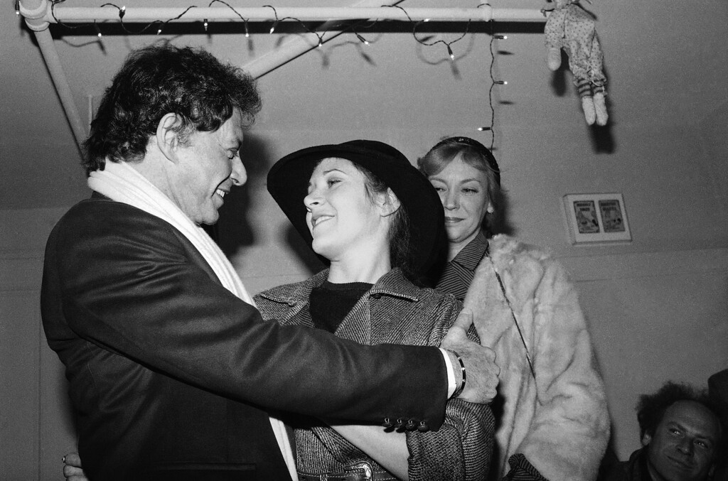 """. Eddie Fisher congratulates his daughter Carrie, backstage at New York\'s Music Box Theater after her debut in """"Agnes of God"""", Jan. 3, 1983. Carrie\'s mother, Debbie Reynolds, who was also in the audience, left the theater without meeting her former husband. (AP Photo/Ray Stubblebine)"""