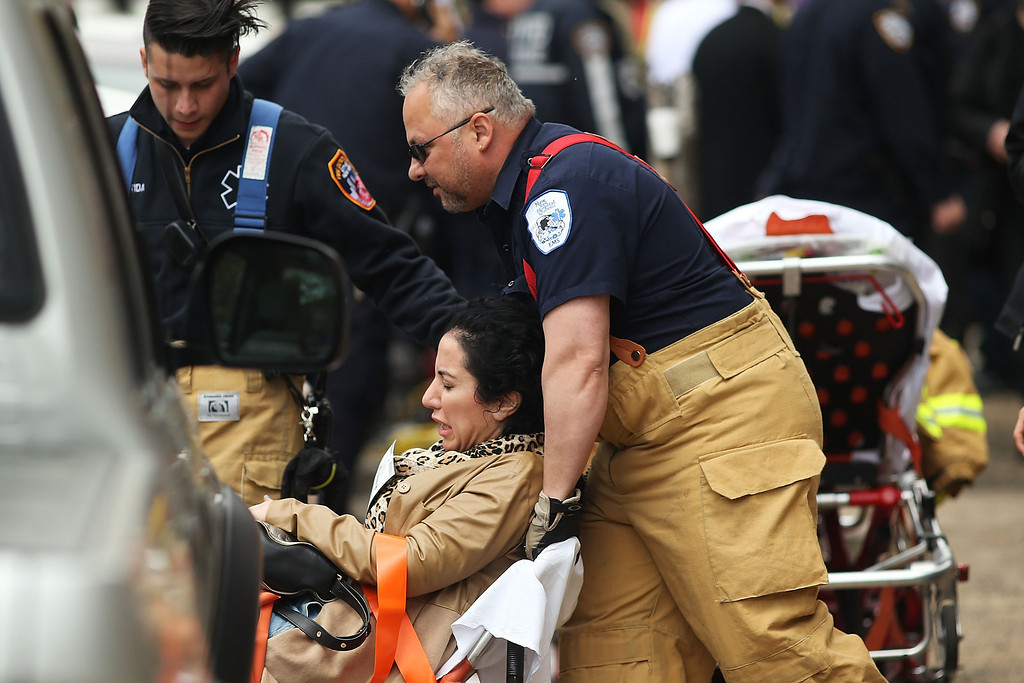 . A woman is aided by New York City firefighters after being evacuated from an emergency staircase following an F train derailment on May 2, 2014 in the Woodside neighborhood of the Queens borough in New York City. According to the Metropolitan Transportation Authority  (MTA) the express F train was bound for Manhattan and Brooklyn when it derailed at 10:40 a.m. about 1,200 feet from the 65th station in Woodside, Queens with hundreds of passengers on board.  (Photo by Spencer Platt/Getty Images)