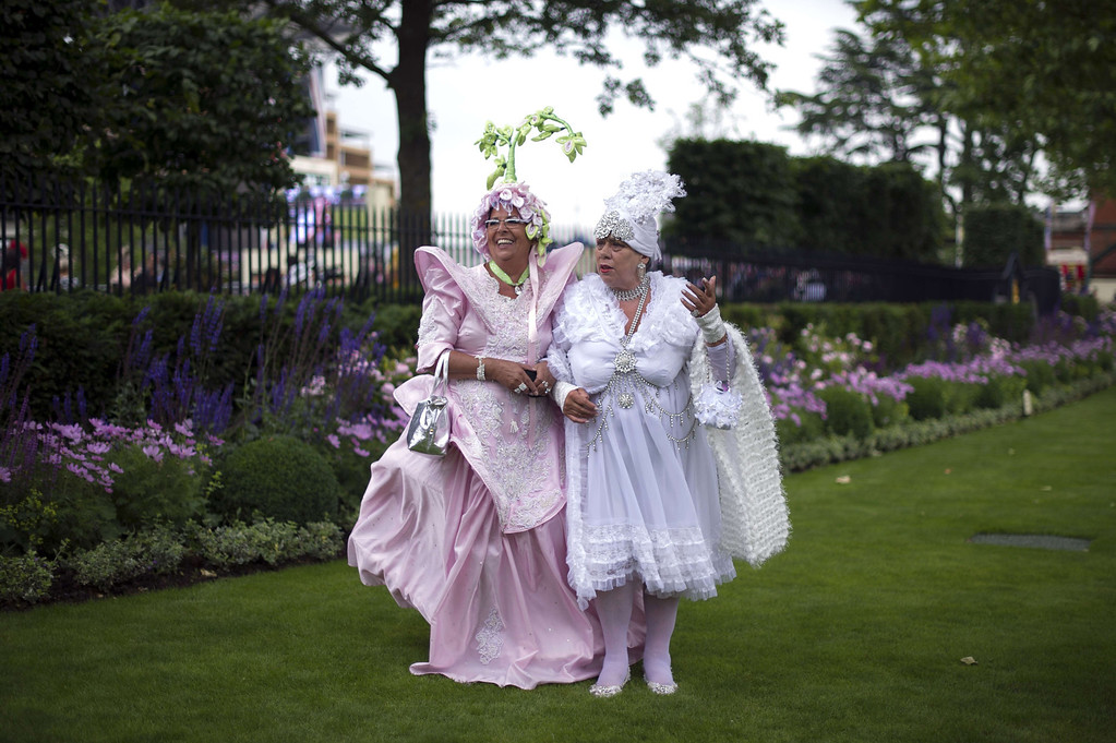 . Race-goers wearing flamboyant costumes pose for photographers on Ladies Day at the annual Royal Ascot horse racing event near Windsor, Berkshire, on June 19, 2014. The five-day annual fusion of high-end fashion and top-class racing is one of the highlights of global horse racing and the pinnacle of the English social calendar. AFP PHOTO / CARL COURT/AFP/Getty Images