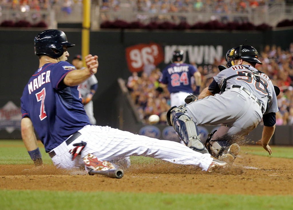 . Minnesota Twins\' Joe Mauer, left, scores on Trevor Plouffe fielder\'s choice as Detroit Tigers catcher Bryan Holaday, right, tries to get the wide throw from third baseman Nick Castellanos allowing Twins\' Kennys Vargas to score on an error by Castellanos in the sixth inning of a baseball game, Friday, Aug. 22, 2014, in Minneapolis. (AP Photo/Jim Mone)