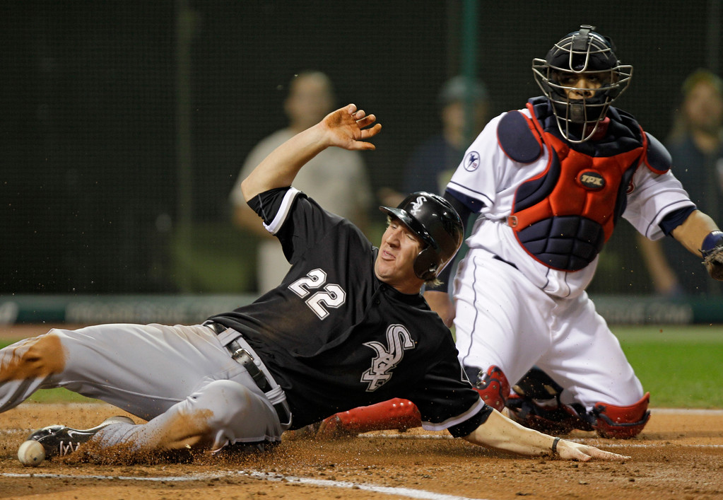 . Chicago White Sox\'s Brent Morel (22) slides past Cleveland Indians catcher Carlos Santana to score in the fifth inning of a baseball game Thursday, Sept. 22, 2011, in Cleveland. Morel went from first to third on Juan Pierre\'s single and scored on a throwing error by Cleveland Indians shortstop Asdrubal Cabrera. (AP Photo/Mark Duncan)