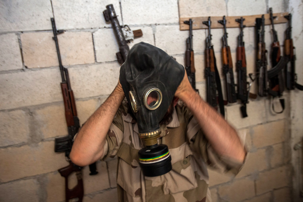 . A Syrian rebel tries on a gas mask seized from a Syrian army factory in the northwestern province of Idlib on July 18, 2013. Western countries say they have handed over evidence to the UN that Bashar al-Assad\'s forces have used chemical arms in the two-year conflict. More than 100,000 people have died in the conflict, which morphed from a popular movement for change into an insurgency after the regime unleashed a brutal crackdown on dissent. DANIEL LEAL-OLIVAS/AFP/Getty Images