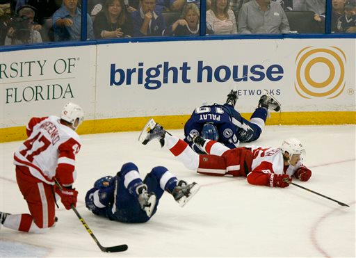 . Detroit Red Wings defenseman Alexei Marchenko (47), Tampa Bay Lightning center Tyler Johnson (9), Lightning left wing Ondrej Palat (18) and Red Wings defenseman Danny DeKeyser (65) tumble after simultaneous collisions during the third period in Game 1 of an NHL hockey first-round playoff series, Thursday, April 16, 2015, in Tampa, Fla. (Douglas R. Clifford/Tampa Bay Times via AP)