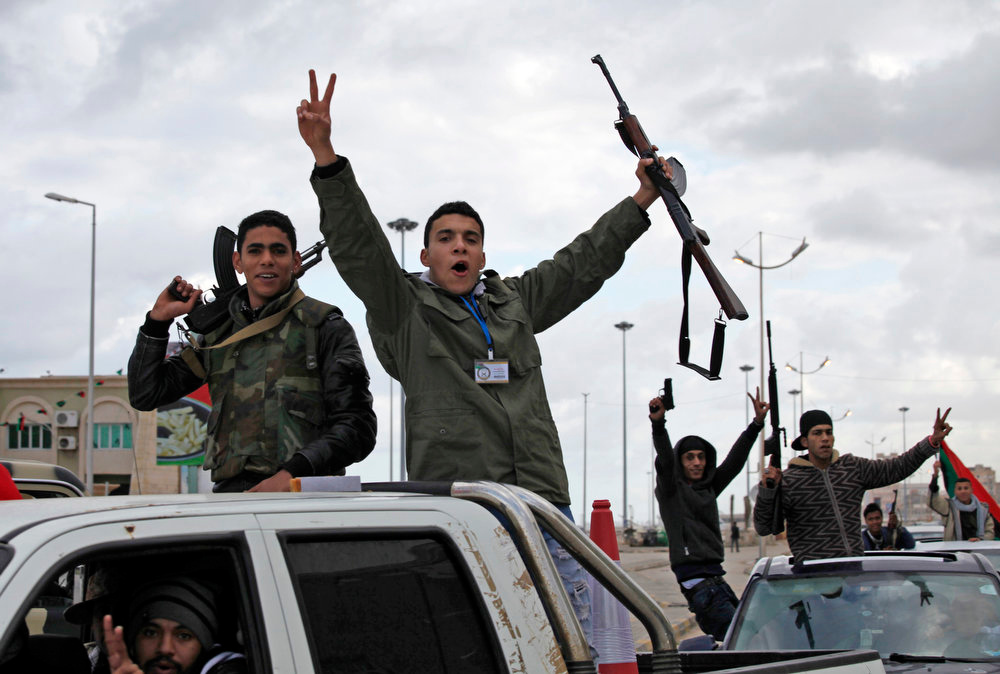 Description of . Libyan gunmen celebrate on the early morning of the second anniversary of the revolution that ousted Moammar Gadhafi, in Benghazi, Libya, Sunday, Feb, 17 2013.  (AP Photo/Mohammad Hannon)