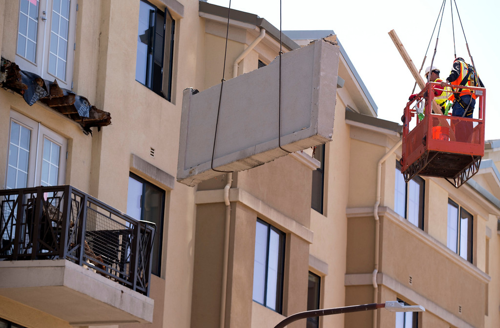 . Workers use a crane to remove the deck of a balcony that collapsed at an apartment building on Kittredge Street, sending 13 people plunging to the street below, Tuesday, June 16, 2015, in Berkeley, Calif. Six people were killed and seven more were transported to area hospitals. (D. Ross Cameron/Bay Area News Group)