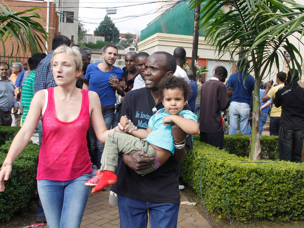 . The mother and a security guard help a child outside the Westgate Mall in Nairobi, Kenya Saturday, Sept. 21 2013, after gunmen threw grenades and opened fire during an attack that left multiple dead and dozens wounded.  (AP Photo/Khalil Senosi)