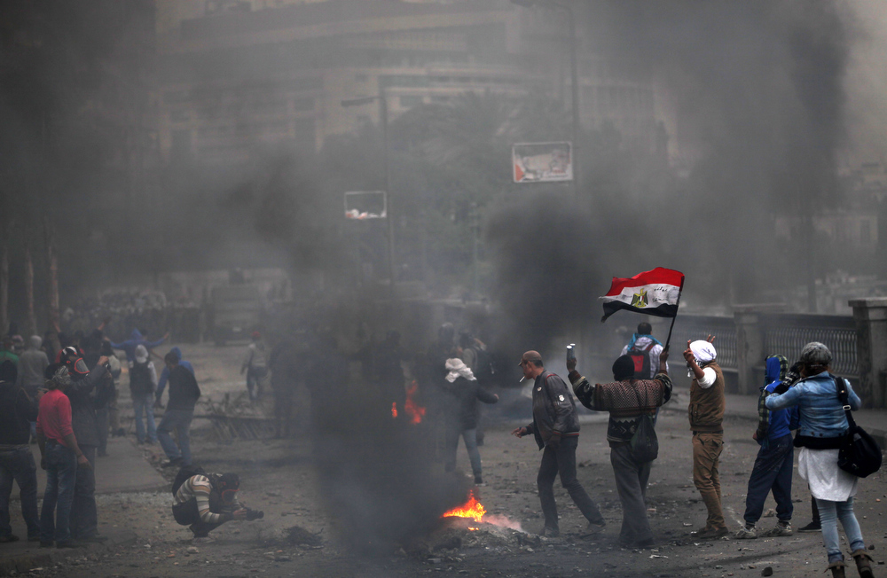 Description of . Egyptian protesters clash with riot police, unseen, near Tahrir Square, Cairo, Egypt, Monday, Jan. 28, 2013. Health and security officials say a protester has been killed in clashes between rock-throwing demonstrators and police near Tahrir Square in central Cairo. The officials say the protester died Monday on the way to the hospital after being shot. (AP Photo/Khalil Hamra)