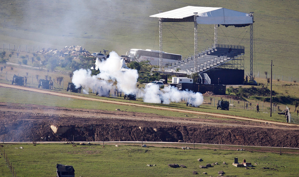 . South African National Defence Forces fire ceremonial cannons as the body of Nelson Mandela is brought from the family home to the funeral tent, prior to his burial, in Qunu, South Africa Sunday, Dec. 15, 2013. (AP Photo/Ben Curtis)