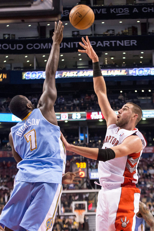 . Toronto Raptors\' Jonas Valanciuna, right, shoots over Denver Nuggets\' Jordan Hamilton during the second half of an NBA basketball game on Sunday, Dec. 1, 2013, in Toronto. (AP Photo/The Canadian Press, Chris Young)