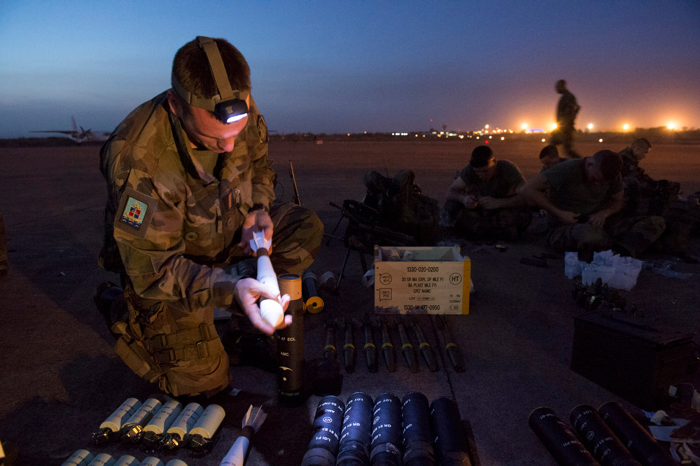 """. In this picture dated Sunday, Jan. 13, 2013 and released by the French Army Communications Audiovisual office (ECPAD), a French soldier of the 2nd Marine Infantry Regiment based in Le Mans, western France, prepares ammunition before distribution at Bamako airport, Mali. An official at France\'s Defense Ministry says the country will \""""gradually deploy\"""" a total of 2,500 troops to Mali, and the French president says the military operation will last until security has been restored and African forces are ready to take charge. (AP Photo/Arnaud Roine, ECPAD)"""