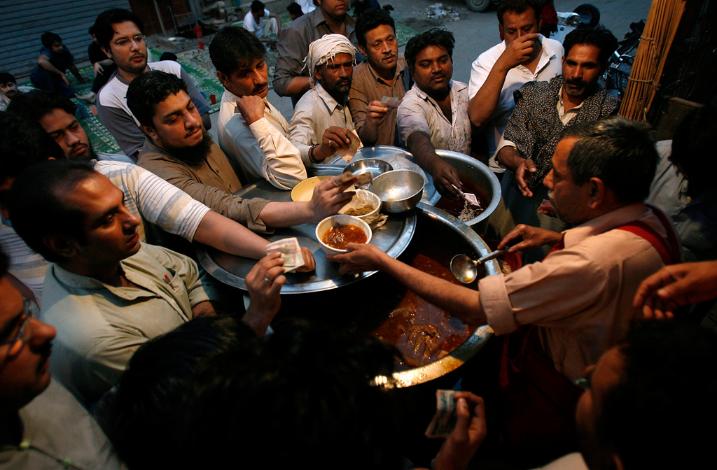 . Men gather to get a bowl of siri paya, a traditional breakfast dish of goat heads and feet, in Lahore\'s Old City early morning April 28, 2009.       REUTERS/Mohsin Raza