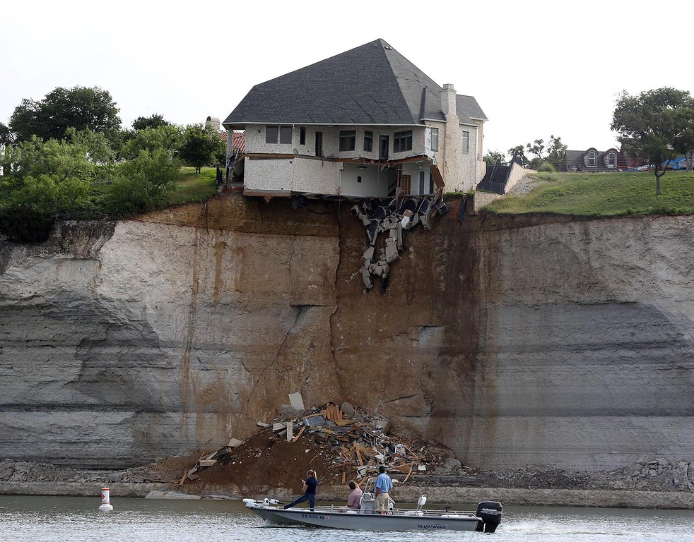 . Boaters examine a $700,000 vacation home perched on a crumbling cliff overlooking Lake Whitney that was later burned to the ground deliberately Friday, June 13, 2014, near Whitney, Texas. The house was condemned earlier after a fracture appeared in the bluff on which it was built. (AP Photo/Waco Tribune Herald, Rod Aydelotte) (AP Photo/Waco Tribune Herald, Rod Aydelotte)