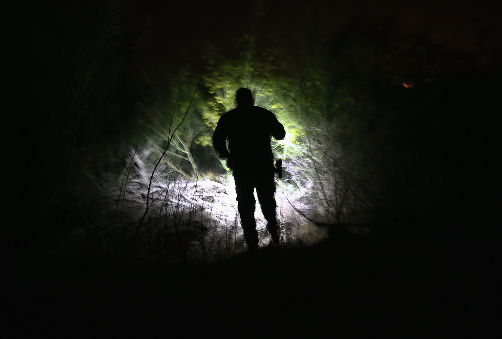 . PENITAS TX - APRIL 11:  A U.S. Border Patrol agent searches in dense brush for undocumented immigrants who had crossed from Mexico into the United States on April 11, 2013 in Penitas, Texas. In the last month the Border Patrol\'s Rio Grande Valley sector has seen a spike in the number of immigrants crossing the river from Mexico into Texas. With more apprehensions, they have struggled to deal with overcrowding while undocumented immigrants are processed for deportation. According to the Border Patrol, undocumented immigrant crossings have increased more than 50 percent in Texas\' Rio Grande Valley sector in the last year. Border Patrol agents say they have also seen an additional surge in immigrant traffic since immigration reform negotiations began this year in Washington D.C. Proposed reforms could provide a path to citizenship for many of the estimated 11 million undocumented workers living in the United States.  (Photo by John Moore/Getty Images)