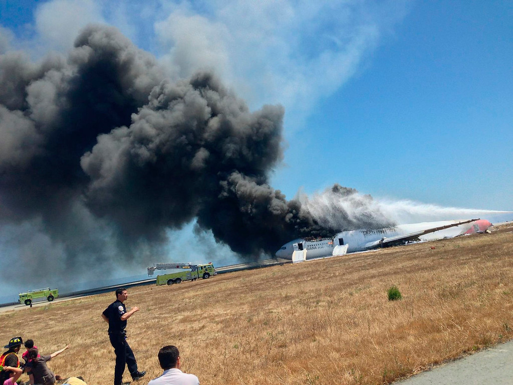 . Asiana Airlines Boeing 777 is engulfed in smoke on the tarmac after crash landing at San Francisco International Airport in California on July 6, 2013 in this photo provided by passenger Eugene Anthony Rah released to Reuters on July 8, 2013.  REUTERS/Eugene Anthony Rah/Handout via Reuters