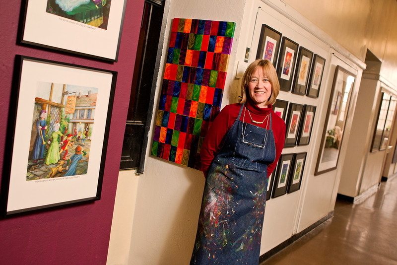 "Resident Artist Deborah (Deb) Loverd has been at The Umbrella since 1996. Equipped with a Bachelor of Fine Arts Degree from Syracuse University, and further art study at Columbia University and the DeCordova Museum School, she finds the collective wealth of experience, shared freely by the artists who have studio space at the Umbrella, a constant inspiration.   One of the major themes in Deb's colorful artwork is the humorous depiction of what she calls ""Portentous Moments,"" found in fables, legends, nursery rhymes and fairy tales. Deb traces her fascination with the important choices made by storybook characters back to childhood. As a young girl listening to ""Little Red Riding Hood,"" she wanted to jump into the story and intervene, ""No! No!"" she would have warned, ""Don't talk with that wolf! Don't do it!"" Deb's caption for this moment in time: ""Red Riding Hood shares her afternoon plans with a stranger.""   You might be curious as to the portentous moment Deb chose for the Sleeping Beauty story. The answer is found in her studio where a painting of Sleeping Beauty in an imagined luxurious bedroom, complete with prince gazing intently down upon her, hangs in her studio. The caption reads: ""The Prince ponders his level of commitment.""   The highly detailed and colorful illustrations portray a moment in children's literature that rings familiar to almost all of us and captures favorite characters including Hansel and Gretel, the three men in a tub, or the cow jumping over the moon. Each scene is a colorful and visual delight, while the captions offer a humorous and thought-provoking point of view. Funny, indeed, yet also serious, the illustrations cause us to ponder new perspectives on the fabled moments.   Deb's ""LetterSpeak"" series, is an inventive collection of paintings based on the shape of the letters of the alphabet. Letters show personality by way of humorous comment to another letter: Capital ""P"" says to ""pot-bellied"" capital ""B"" ""I warned you to lay off the carbs."" A simple ""F"" looks at a flowery Victorian ""F"" and quips, ""No. No one will notice you've had a 'little work' done.""   The artist's medium of choice is gouache, an opaque watercolor with extremely vibrant hues. She sketches out the design on tracing paper, before transferring it to a sheet of Lanaquarelle, a fine-arts watercolor paper. This high quality cotton paper absorbs many layers of color and is sturdy enough for vigorous brushwork. After Deb lays the base colors down, she slowly builds layer upon layer to provide depth and richness, wetting the areas that she'll paint, adding color, dabbing it with tissue, repeating the process as many times as she feels is necessary to get the desired effect. ""The multiple layers make the picture more lively,"" says Deb.   The tiny details that are added as the last step of the process are the hallmark of Deb's painting style. ""The details are the dessert,"" she says, and with very sharp colored pencils, she punches up little areas to make the color ""pop."" Deb acknowledges that the painting is finished when she stands in front of it with a pencil or paintbrush and can't find a spot that needs anything.   Not all Deb's paintings are part of these two major series. Her walls also hold pastoral scenes of yesteryear in ""New England Spirit"" and ""Welcoming Shade."" In ""Literary Lights of Concord,"" Deb pays tribute to Concord authors, past and present. There are also acrylic paintings—many boast a bold graphics style or display her signature touch of whimsy and humor—adorning the walls of her Umbrella studio space.   Deb looks forward to Open Studio days, when she welcomes visitors to her space. ""I like to hear the ideas and suggestions that people have for future work,"" she says.   Deb is delighted that select pieces of her work have been exhibited in such venues as the Concord, Fowler, Carlisle (Gleason) and Bedford Libraries, Concord Art Association, Trinity and TriCon Churches in Concord, as well as various art galleries."