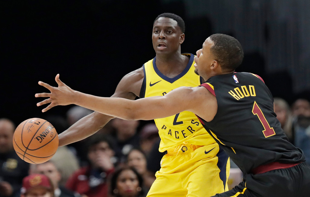. Indiana Pacers\' Darren Collison (2) passes around Cleveland Cavaliers\' Rodney Hood (1) in the first half of Game 1 of an NBA basketball first-round playoff series, Sunday, April 15, 2018, in Cleveland. (AP Photo/Tony Dejak)
