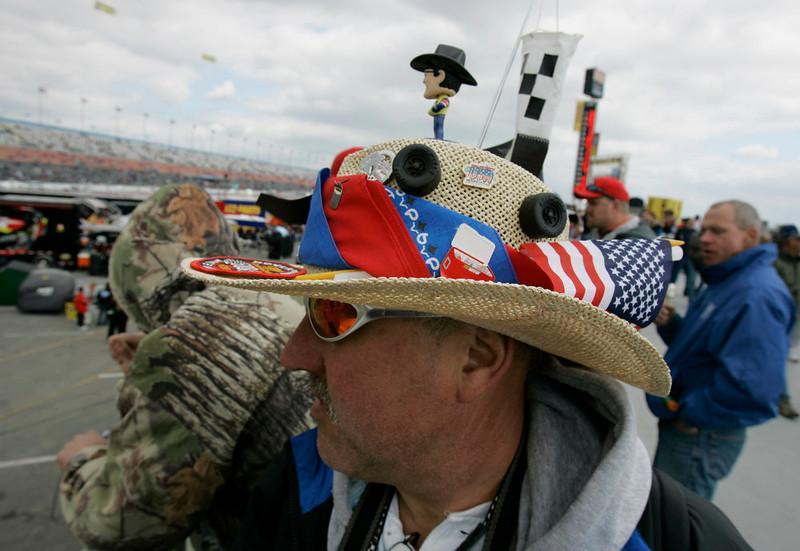 . Dave Powell, of Glen Burnie, Md., wearing a racing-themed hat, walks in the infield at Daytona International Speedway in Daytona Beach, Fla., Sunday, Feb. 18, 2007, before the NASCAR Daytona 500 auto race. (AP Photo/John Raoux)