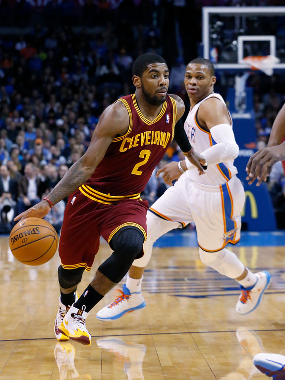 . Cleveland Cavaliers guard Kyrie Irving (2) drives past Oklahoma City Thunder guard Russell Westbrook (0) in the first quarter of an NBA basketball game in Oklahoma City, Wednesday, Feb. 26, 2014. (AP Photo/Sue Ogrocki)